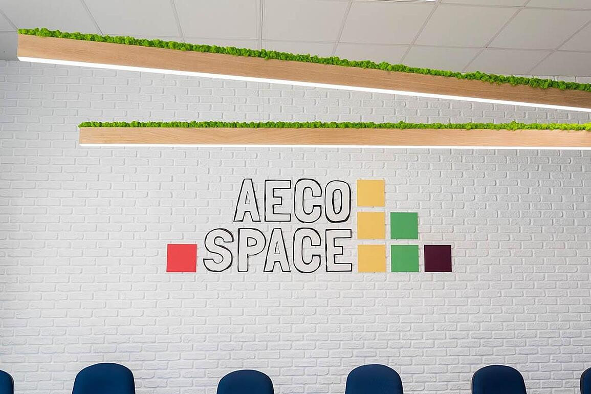 AECO Space logo on white brick wall and 6m long bespoke lamps covered with green moss.