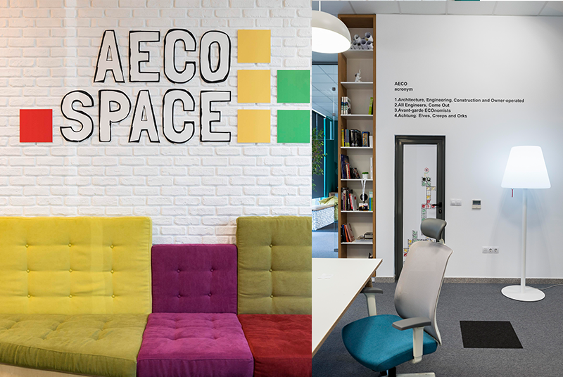 The AECO Space logo on white brick wall and colorful sofa.